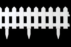Plastic fence for flowerbeds. On a black background stock photos