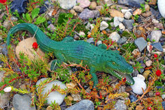 Plastic figure of a crocodile on the rock garden Royalty Free Stock Photo