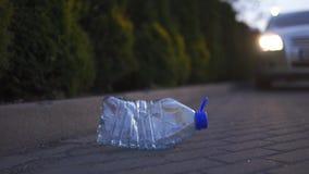 Plastic fles die op de grond bij nacht voor een Weggegooide auto liggen - gerecycleerd niet - Afval en verontreiniging van stock footage