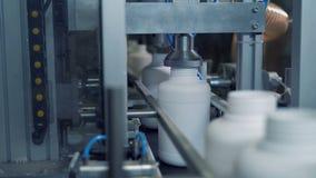 Plastic flessen die door het drukken van mechanisch materiaal gaan stock video