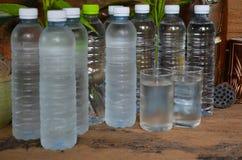 Plastic flessen en glazen koel water stock foto's