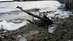 Plastic flessen en glazen op het zandige strand Vuil water waarin het zllichny huisvuil drijft Wit schuim op de kust stock footage