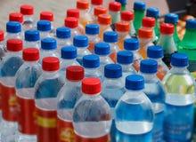 Plastic flessen met dranken en kleurrijke deksels stock afbeelding
