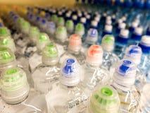 Plastic flessen met mineraalwater Close-up op waterflessen in ruw en lijnen Plastic flessen, kleurrijke kappen Plastic flessenver royalty-vrije stock foto