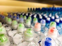 Plastic flessen met mineraalwater Close-up op waterflessen in ruw en lijnen Plastic flessen, kleurrijke kappen Plastic flessenver stock foto