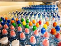 Plastic flessen met mineraalwater Close-up op waterflessen in ruw en lijnen Plastic flessen, kleurrijke kappen Plastic flessenver stock fotografie