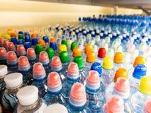 Plastic flessen met mineraalwater Close-up op waterflessen in ruw en lijnen Plastic flessen, kleurrijke kappen Plastic flessenver stock foto's