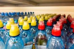 Plastic flessen met water, kleurenkappen royalty-vrije stock foto
