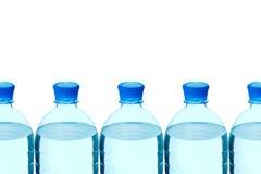 Plastic flessen mineraalwater in een rij Stock Afbeeldingen