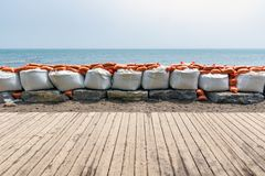 Plastic flood protection sandbags stacked into a temporary wall. White and orange plastic flood protection sandbags stacked into a temporary dam royalty free stock photos