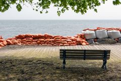 Plastic flood protection sandbags stacked into a temporary wall. White and orange plastic flood protection sandbags stacked into a temporary dam stock images