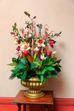 Plastic flower arrangement in golden vase Stock Images