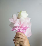 Plastic flower bouquet in hand on grey background Stock Photos