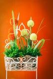 plastic flower on orange wall background Royalty Free Stock Image