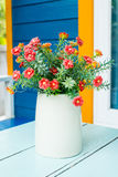 Plastic flowers. In pot on blue table stock images