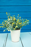 Plastic flowers. In pot on blue table Royalty Free Stock Photos