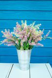 Plastic flowers. In pot on blue table Royalty Free Stock Images