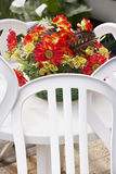 Plastic flowers on table. Basket with plastic flowers on white plastic garden table with chairs around stock image