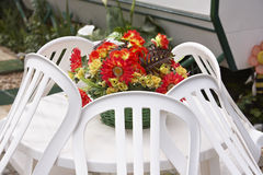 Plastic flowers on table. Basket with plastic flowers on white plastic garden table with chairs around royalty free stock image