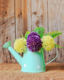 Plastic flowers and vase. On the wooden background Stock Images