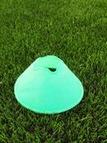 Plastic football green turf playground with grinded black rubber in core and bright green blue plastic cone. Stock Image