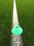 Plastic football green turf playground with grinded black rubber in core and bright green blue plastic cone. White line marks Royalty Free Stock Photos