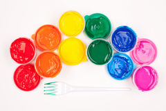 Plastic fork and color paints. Motley paints on the white background. paints arranged as rainbow with plastic fork partly colored in green paint. studio shot Royalty Free Stock Photo