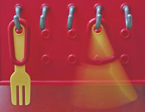 Plastic fork and knife. A toy fork and a knife twisting on the red plastic hanging place of the toy kitchen Stock Photos