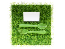 Plastic fork and spoon on green grass , space for text Stock Photo