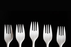 Plastic Forks. Five white plastic forks in a row shot on a black background Royalty Free Stock Photo