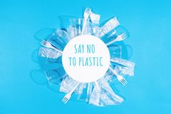 Plastic forks, bags and cups on blue background. stock photos