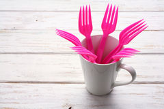 Plastic Forks and Cup. On Wooden Background royalty free stock photos