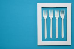 Plastic forks for picnics in a white frame on a blue background. Top view, minimalistic trend.  royalty free stock images