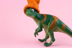 Plastic funny green dinosaur. Funny green dinosaur toy in little knitted orange hat near on pastel pink background royalty free stock photos