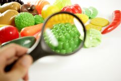 Plastic game, fake varied vegetables and fruits. Children food education toy. Looking with amplifier lens royalty free stock image