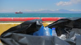 Plastic garbage packed into bag on ship in sea. Plastic from the sea on seascape background. Ship on the horizon while. Avoid plastic packaging. Garbage can full stock video footage
