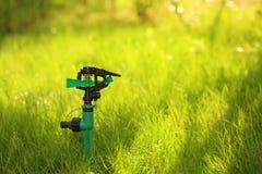 Plastic garden splinkter. Standing on the groud in the gazon grass Stock Photo
