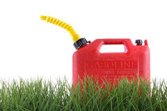 Plastic gas can in grass against white. Background royalty free stock photography