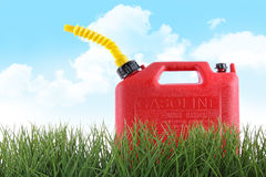 Plastic gas can in grass against white. Background stock image