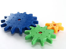 various sizes of colorful plastic gear wheels (green blue and yellow color) connecting isolated on white background stock photography