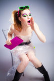 Plastic girl. Young woman in plastic dress and heavy make up  calling for someone  studio shot Royalty Free Stock Photos