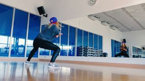 Plastic girl dancing the hip-hop in front of mirror. In the gym. The dancer raise up the hands, taking a steps backward and moving her body. Young beautiful stock video