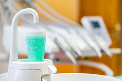 Plastic glass with antiseptic rinsing liquid in the dental cabin Royalty Free Stock Image