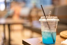 Glass of blue lemon soda in beverage cafe, Space for creative ideas. Plastic glass of blue lemon soda in beverage cafe, Space for creative ideas stock photography
