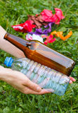 Plastic and glass bottle in hand of woman, littering of environment Royalty Free Stock Image