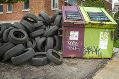 Plastic glass metal paper cardboard tires recycling. Large industrial heavy car used tires piled up in beside a sidewalk where peoples walks every day stock image