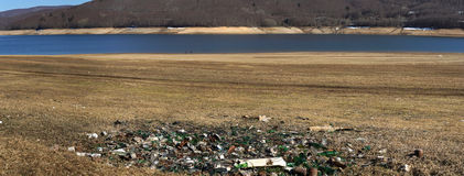 Plastic glass  metal and paper waste on the lakeside Panorama Royalty Free Stock Photo