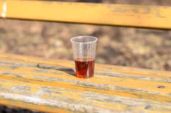 Plastic glass on park bench. Plastic glass with red beverage liquid close-up on old painted yellow wooden bench in park royalty free stock images
