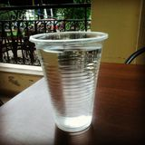 Beaker of water. Corrugated transparent plastic beaker of water on polished brown wooden bar surface (in Corfu Greece Stock Photography