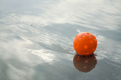 Plastic golf ball. Orange plastic practice golf ball on the beach Stock Photos